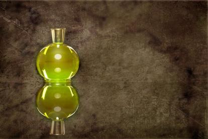 Gruener Parfum Flakon hinter textiertem Hintergrund mit spiegelung-#parfum
