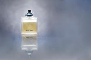 Parfum Flakon hinter grauem Hintergrund und auf Glasplatte-#parfum