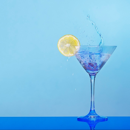 splashing martini with lemon and blue background
