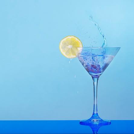 splashing martini with lemon and blue background
