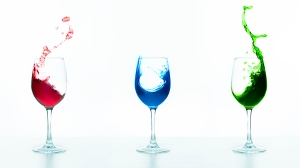 three wine glasses with splashing liquids in red, blue and gree